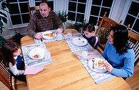 Family eating pizza at dinner table