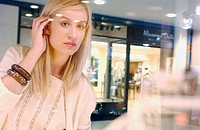 Woman in shopping center, looking at shop windows