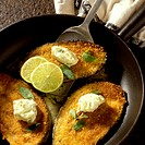 Breaded aubergine slices with herb butter in pan