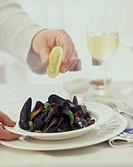 Sprinkling steamed mussels with lemon