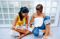 Girls sitting down on the floor with mobile phone