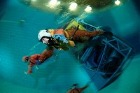 Water crash simulation. Aircraft pilot escaping from a replica (centre right) of an aircraft cockpit that has been plunged into a pool of water to re...