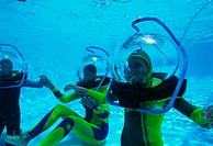 Tourist divers practising at  the bottom  of  a swimming pool.  The diving helmet is connected by a tube to a  pumped  supply  of  air. This  allows  ...