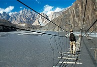 Man crossing suspension bridge, Karakorum, Pakistan