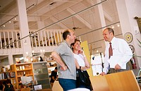 Couple and salesman talking in a furniture store