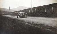 Photograph by H Wade of a racing car driving along a country road.