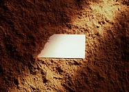 Piece of paper partly covered with dirt, light shining across