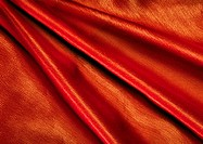 Folds in orange fabric, close-up, full frame