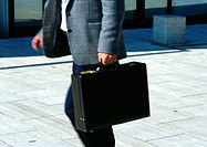 Man walking with briefcase, mid section, blurred motion