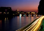 France, Paris, cars traveling on quai next to River Seine at night, blurry