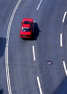Red car on road with white lines, high angle view, full frame