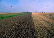France, Lorraine, plowed field with hot air balloons in distance