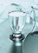 Glass of water with carafe blurred in foreground