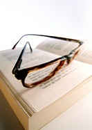 Glasses laying on open book, close-up