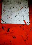 Black splatters on white and red plastic