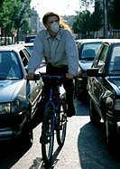 Person riding bike in between cars with pollution mask on