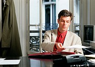 Man sitting at desk, holding paper (thumbnail)