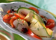 Zucchini, tomato and scallop dish with herbs, close-up