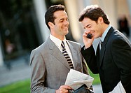 Two businessmen side by side outside, one using cell phone