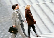 Three business people walking, blurred