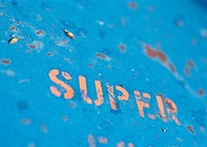 ´Super´ text stenciled on rusty surface, close-up