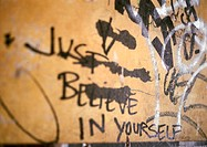 'Just believe in yourself' written text and graffiti on wall, close-up