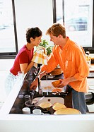 Couple smiling face to face over counter, man washing dishes, woman drying bowl