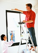 Man standing on ladder, painting wall, woman holding up brush