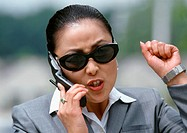Woman holding cell phone, portrait (thumbnail)
