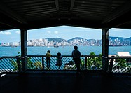 Hong Kong, silhouettes of an adult and two children leaning on rail, rear view, city in distance