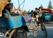 China, Beijing, person sitting in rickshaw, side view