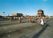 China, Beijing, Tiananmen Square, people walking with and riding bikes in street