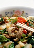 Chopsticks in dish of meat and vegetables, close-up