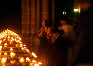France, Paris, Notre Dame Cathedral, people praying next to candles