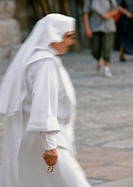 Nun walking in street, side view