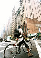Man riding bike in street, buildings in background