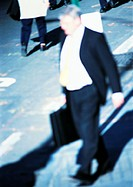 Businessman walking in street, blurred