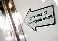 'Entrance at revolving door' text on arrow sign, close-up