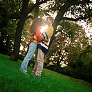 Young man and woman standing on grass, embracing, side view, full length