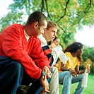Young people sitting together on bench outside, some with sandwiches