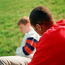 Two young men, one sitting on grass