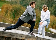 Man and woman stretching legs together on wooden walkway