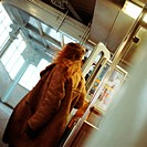 Young woman walking through doors in subway station
