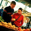 Young couple looking at fruit at outdoor market, fruit blurred in foreground