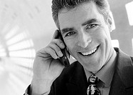Businessman talking on cellular phone smiling at camera, close-up