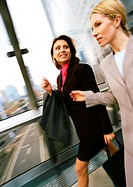 Businesswomen walking together in elevated passageway, blurred