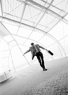 Businessman dancing with briefcase in hand, b&amp;w