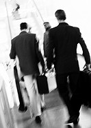 Business people walking to escalator, rear view, blurred, b&amp;w