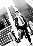 Businessman getting off escalator, running and holding briefcase, blurred, b&amp;w