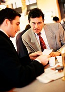 Businessmen looking at paper over coffee